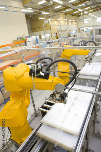 Robotic arms working on factory assembly line