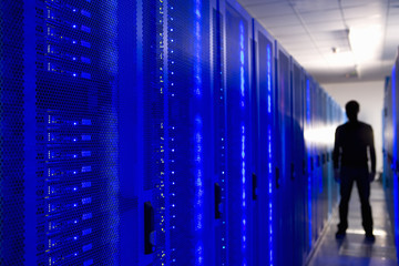 Silhouette of man in network server room