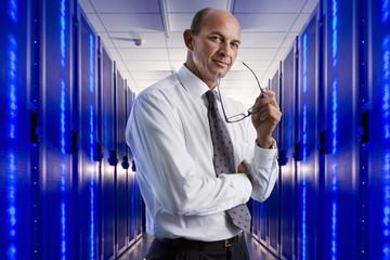 Portrait of businessman in network server room