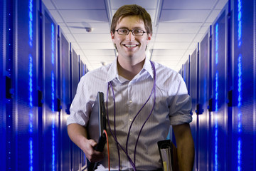 Portrait of smiling IT technician with laptop and LAN cables in network server room