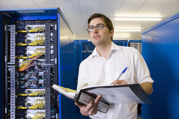 IT technician with binder in network server room