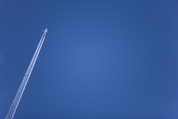 Airplane with contrail flying in clear, blue sky