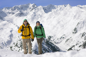 Portrait of happy couple holding hands and backpacking on snowy mountain