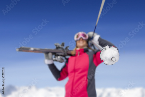 Woman holding skis and ski poles