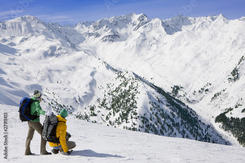 Couple with backpacks looking at view of snowy mountains