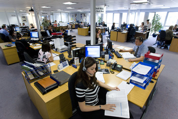 Sales people working at desks in call center office