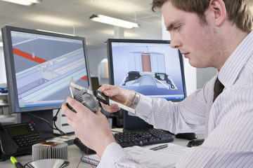 CAD designer measuring part at desk in office