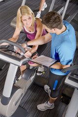 Personal trainer with clipboard guiding woman on exercise bike in health club