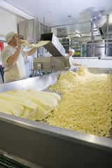 Cheese maker grating farmhouse cheddar with machine