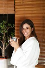 entspannte Frau im Bademantel zuhause mit tee oder Kaffee