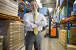 Portrait of smiling businessman with arms crossed in warehouse