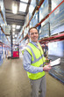 Portrait of smiling warehouse manager holding clipboard and walkie-talkie