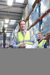 Portrait of smiling warehouse manager and worker with clipboard and pallet truck