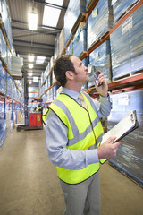 Warehouse manager holding clipboard and using walkie-talkie