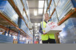 Portrait of smiling warehouse worker holding boxes in warehouse