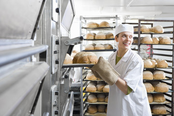 Baker removing fresh loaves of bread from oven