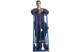 Worker in coveralls standing with hand truck