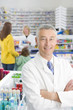 Pharmacist in pharmacy with customers in background