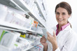 Pharmacist reading medicine bottle in pharmacy