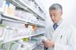 Pharmacist reading medicine bottle in pharmacy