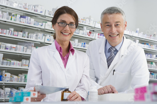 Pharmacists filling bottle with medicine in pharmacy
