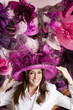 Customer trying on ornate pink feathered hat in shop