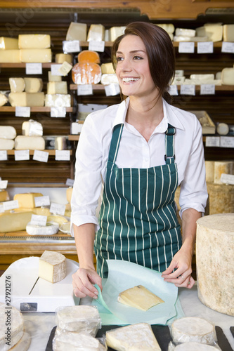 Saleswoman standing at counter wrapping wedge of cheese in cheese shop