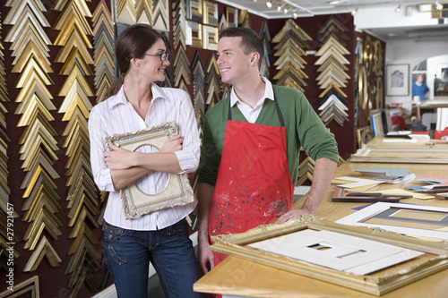 Salesman and customer standing in frame shop