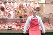 Butcher standing in front of butcher shop window