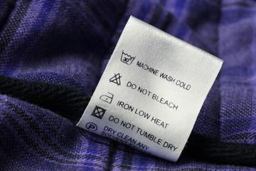 Laundry care label on scotch textile background