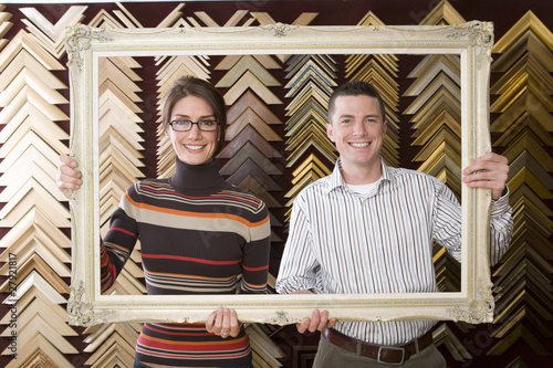 Clerks lifting gold frame in frame shop
