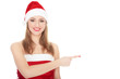Smiling woman in Santa red hat pointing on blank space