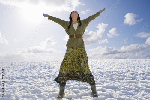 Exhilarated woman standing in snowy field