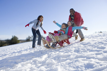Father, mother and daughters sledding on snowy hill