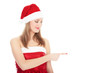 Smiling woman in Santa red hat pointing on blank space.