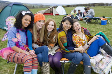 Laughing friends camping and attending outdoor festival