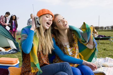 Young women wrapped in blanket and listening to radio at outdoor festival