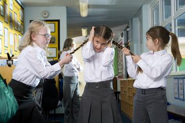 Mean, aggressive school girls teasing and pulling classmates braids