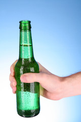 Bottle of beer in hand on blue background