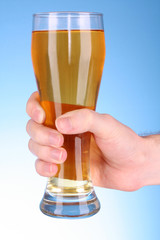 Cup of beer in hand on blue background