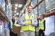Portrait of smiling warehouse manager and workers with clipboard and cardboard box