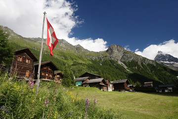 Swiss flag flies above the town of Gruben in Switzerland
