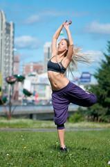 Woman dancing over green city street