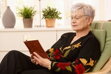 Pensioner reading in armchair poster