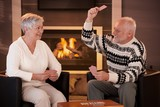Retired couple playing cards in front of fireplace poster