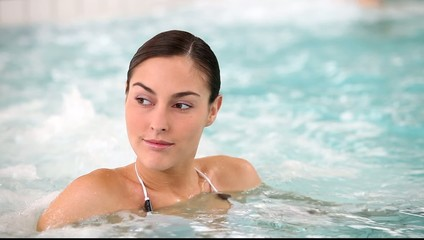 Young woman in spa relaxing in jacuzzi water