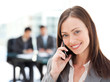 Captivating businesswoman on the phone while her team is working