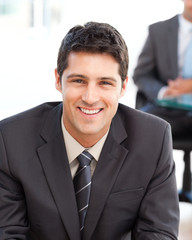 Happy businessman in the foreground during a meeting with a frie