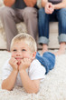 Cute little boy lying on the floor and watching television with