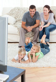 Adorable siblings watching television with their parents lying o